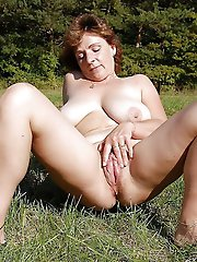 Lascivious mature dame posing undressed outdoors